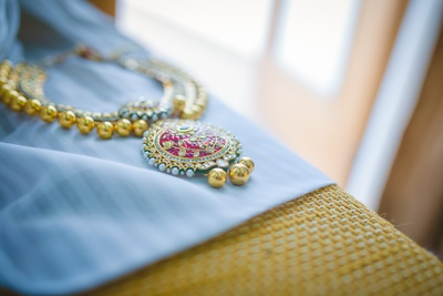 Heirloom gold wedding necklace studded with precious gemstones, diamonds, polki, pearls and large gold bead drops