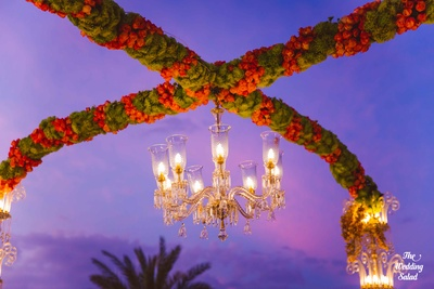 Vedi mandap decorated with ferns and orange Roses and an elegant crystal chandelier