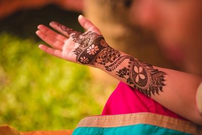 Hands filled with beautiful arabic mehendi design.