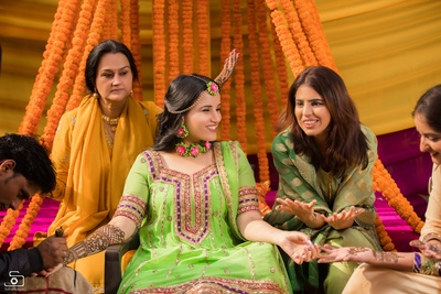The bride is having a gala time while mehendi is being applied on her arms as part of her mehendi ceremony!