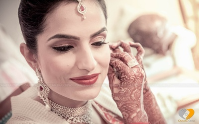 Bride decked in diamond jewellery set adorned with shimmer eye makeup and red lipstick