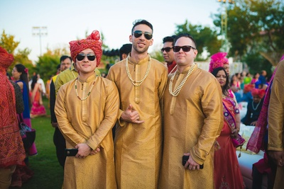 Groomsmen dressed up in coordinated brown color kurtas styled with multi stringed pearl neckpiece.