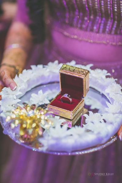 The engagement ring decorated in a beautiful way, amidst white flowers.