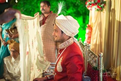 Groom at his wedding ceremony wearing ravishing red sherwani !