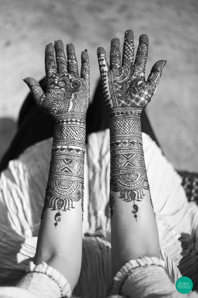 Arms covered in intricately patterned mehendi designs