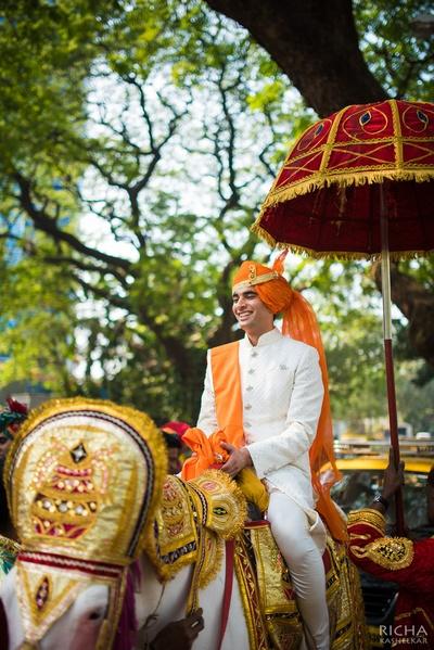 Off-white sherwani embellished with button details and kesari safa and dupatta adorned with Kalgi