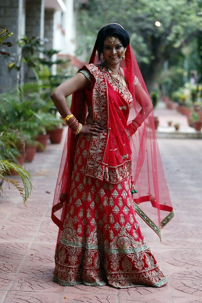 Traditional red bridal lehenga featuring intricate zardosi work along with a sheer red dupatta