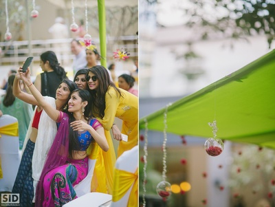 Bridesmaids taking selfies on Mehendi ceremony.
