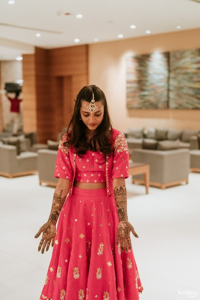 the bride in fuschia pink lehenga with jacket for her mehendi ceremony