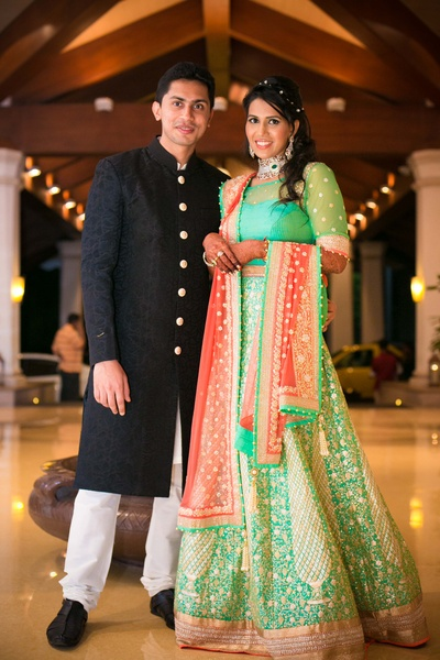 Mint green and coral lehenga embellished with gold thread work, illusion neck choli and coral adorned dupatta enriched with diamond jewellery for the reception party