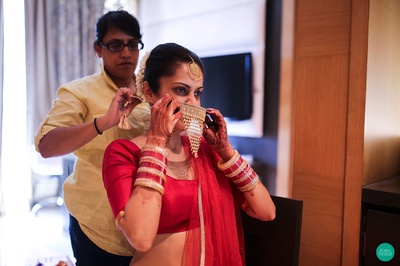 Getting ready for her most special way in all red and heirloom gold jewellery
