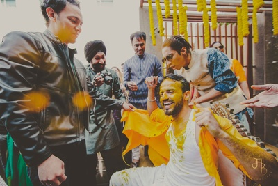 Groom's friends and family tearing his kurta and having fun at the haldi ceremony