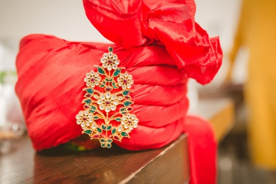 Red Safa styled with ornamented floral Kalgi