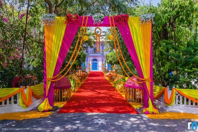 Pink, orange and yellow color coordinated decor with matching drapes, floral bouquets, canopy stands, red carpet and bed of roses