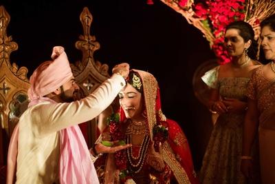 The groom applying sindhoor to his new bride