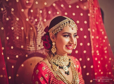 Bride getting ready in a red sabyasachi lehenga for her wedding day