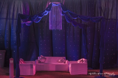 Semi tent with background of mirror work sheer curtains, sofa set and chandelier