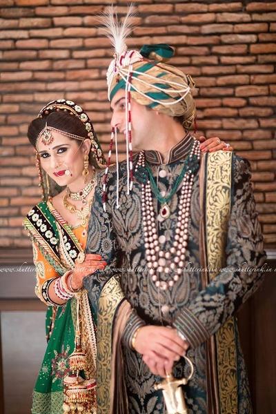 Hunter green Sherwani embellished with paisleys thread work with gold bordered dupatta, green and gold Safa and jadau jewels