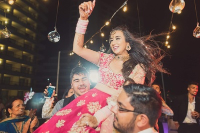 Bridal entry to the reception ceremony with the bride in a fuschia lehenga with gold motifs