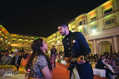 groom with a guitar singing a song for his bride at the sangeet ceremony