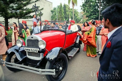 Red Vintage open car escorting the groom.