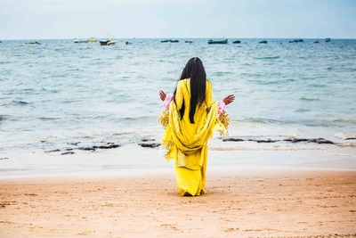 Dressed in a yellow outfit for the beach side chooda ceremony. Beach side photography ideas by Rajesh Luthra