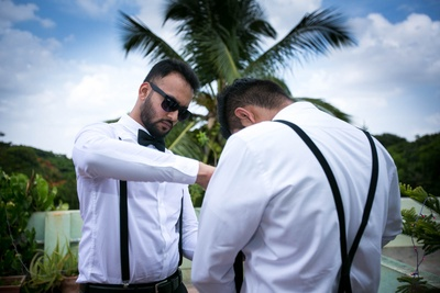 Groomsmen in white shirts and black pants with black suspenders.