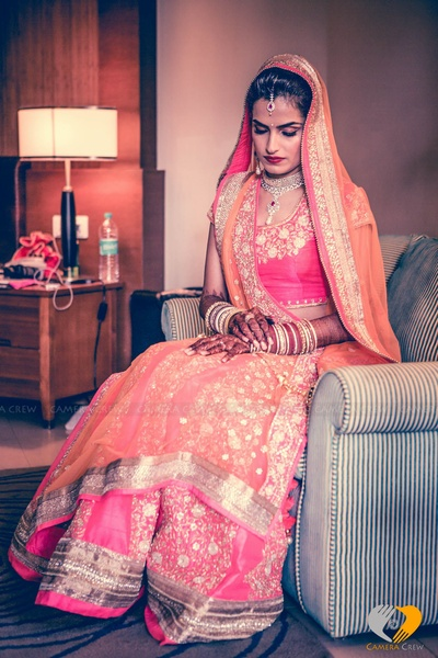 Blush pink and coral lehenga embellished with thread and stone work