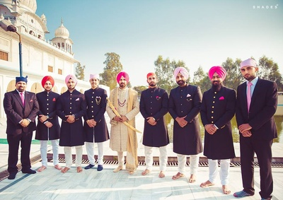 Groomsmen dressed up in black outfits paired with pastel turbans.