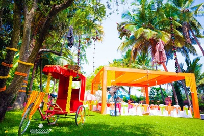 Outdoor wedding venue decorated in hues of orange, yellow and fuchsia, with drapes, tents, tie-backs, Marigold strings and ethnic hanging