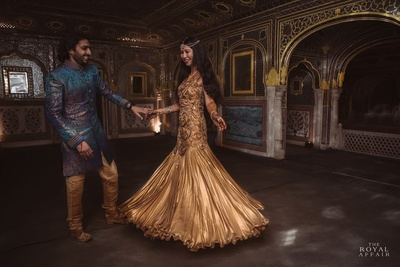 Bride wearing gold fishtail silk gown with heavy embroidery styled with a multi string pearl necklace and diamond kadaas. Groom Compliments her in a multi hue blue bandhgala with silk cream chooridar and moojris.