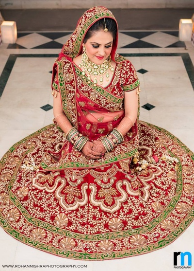 Deep maroon bridal lehenga bedazzled with paisley and gold zari worked details, sequins and thread work