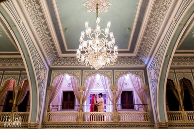 Gorgeous bridal shot inside Chomu Palace with the chandelier as the focal point