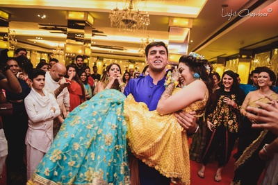 Candid shot of the groom carrying the bride at their mehndi function at The Imperia Hotel, New Delhi