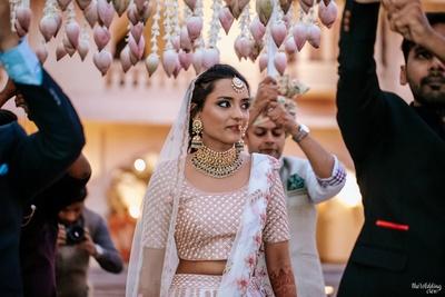 candid capture of the bride walking under a phoolon ki chadaar at her wedding