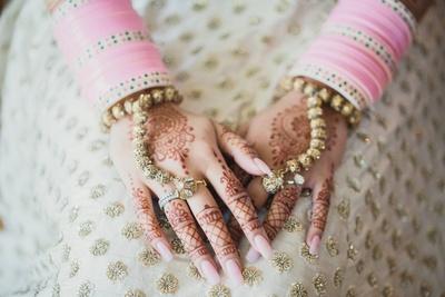 Bridal mehndi design paired with minimal hath phool jewellery