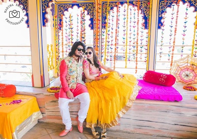 Kriti in yellow and pink lehenga and Rohan complementing her in pink kurta and white pajama styled with colorful floral nehru jacket.