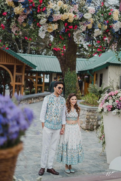 The bride and groom in coordinated blue and white outfits by Anita Dongre at their pre wedding brunch