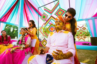 The bride and groom trying hard to avoid the haldi being rubbed on their faces