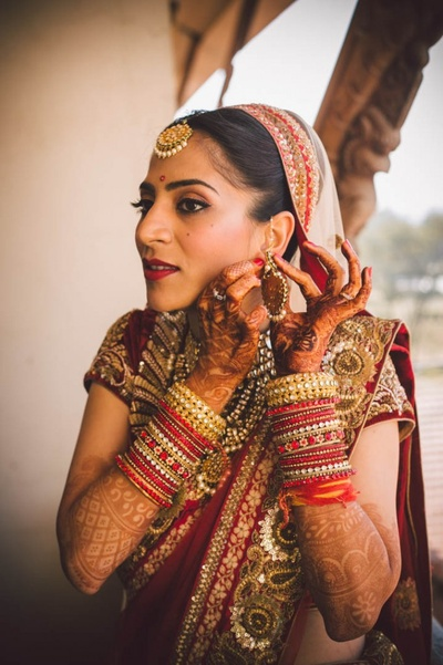 Bride adorned with red and golden lehenga