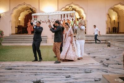 a candid capture of the bride walking under a phoolon ki chadaar