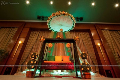 Wooden cradle decorated with pomenders Marigold flowers, cushions and arbor encircled with floral arrangement