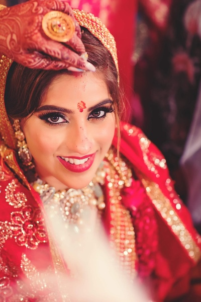 A beautiful shot of the bride while the groom put sindoor onto her forehead.