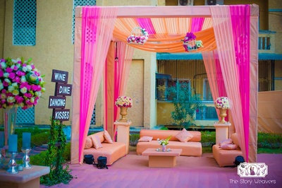 Outdoor canopy set up with gorgeous drapes in hues of pink, peach and orange with floral vases and birdcages to accentuate the decor
