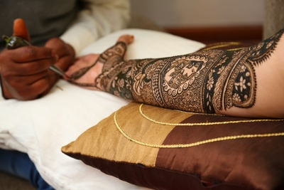 Hand filled with intricate bridal mehendi with bride and groom motifs !