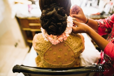 Bridal bun with pastel pink flower decorated around.