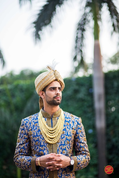 The groom posing in a blue sherwani