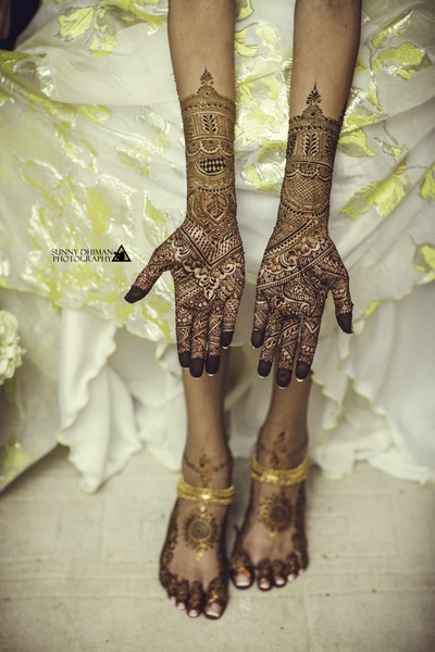 Close up of the bride's feet and hand mehendi design