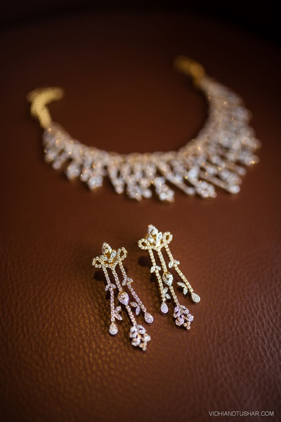 Intricately designed gold ear rings set embedded with diamonds