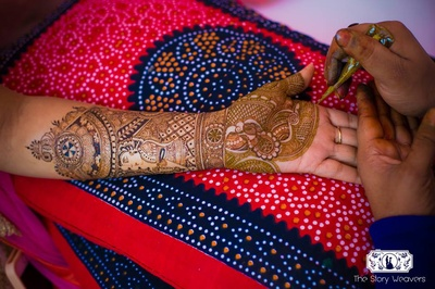 An intricate bridal mehndi design featuring carricatures of the bride with gorgeous ethnic Indian mehndi designs